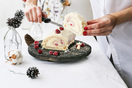 the Christmas log cake with berries and white chocolate in white kitchen 스톡 콘텐츠