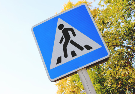 Road sign pedestrian crossing on the background tree and blue sky Stock Photo