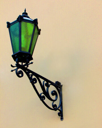 Old lantern with a green glass on a light brown wall of an old house. photo
