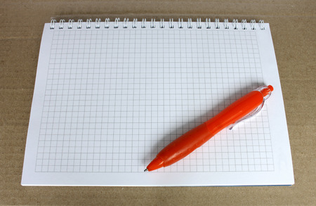 Orange ballpoint pen on the Notepad with a blank page in the box. Notepad on rough brown paper. photo