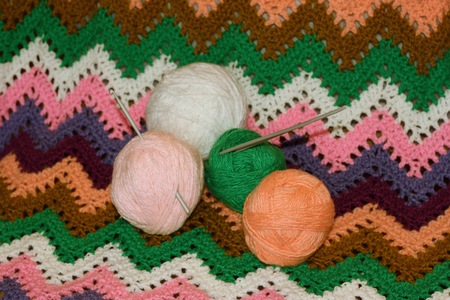 knitting needles: The balls of yarn for knitting, crochet and knitting needles on the associated colored canvas Stock Photo