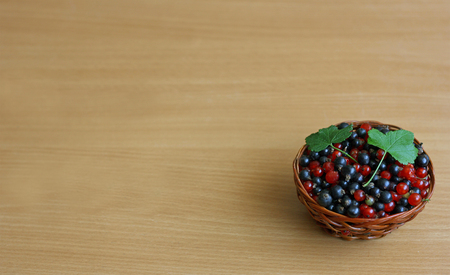 redcurrant: Small brown wicker basket filled with ripe blackcurrant and redcurrant, in the corner of the wooden surface.