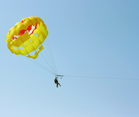 Tourists interested in parasailing, flying in the blue sky.