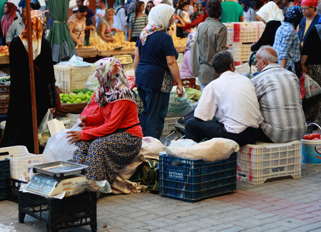tradeswoman: ALANYA, TURKEY - August 28, 2015: Imported temporary market in the city centre of Alanya. A crowd of local men and women selling and choosing products.