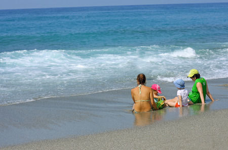 bathing suits: MAHMUTLAR, TURKEY - AUGUST 23, 2015: a Group of two women and two children in bathing suits sitting on the beach and admires the restless blue sea with waves. Editorial