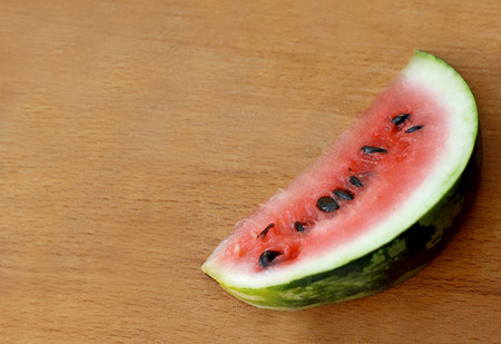rested: Part of a large ripe watermelon rested on an old scratched wooden surface. Cut off a slice .