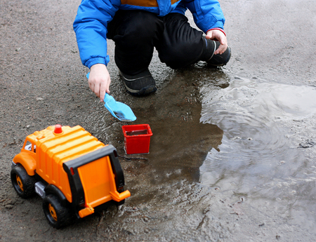 pranks: Kids games fresh air. The portion of a child playing with toys in a mud puddle.