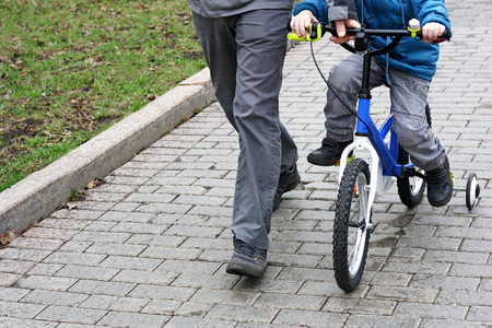 kiddie: The image of the child who is sitting on a kiddie bike with training wheels. Near the child is an adult, and supports the bike.