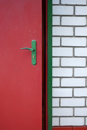 poorly: Iron red painted door in a brick house. The image of the entrance to the house. The door is poorly painted. The brick in some places peeled. Stock Photo