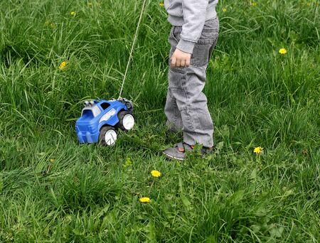 pull toy: La imagen de un niño vestido con pantalones grises y una camiseta. El niño que juega entre la hierba verde gruesa en la calle. Niño jugando con coche de juguete: el coche lleva la cuerda.