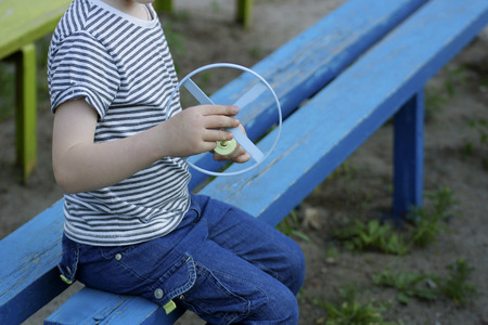 spinner: The image of the boy sitting on the blue old bench. In the hands of a boy toy spinner.