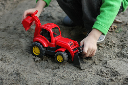 Children play in the fresh air. Boy playing with a red plastic car, a digger in sand. Stock Photo