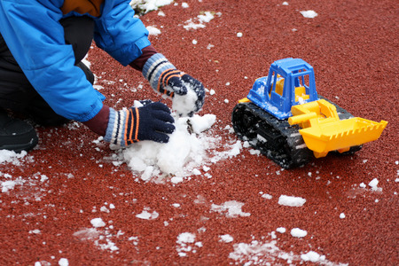 Part of the image of a small child, sitting on the Playground next to the first snow and playing with colorful toy construction equipment. Visible hand, dressed in a blue jacket, black pants and boots.
