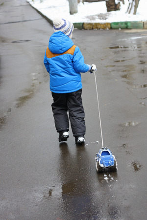 avid: A small child (avid rear), which stands on the wet pavement and holds the rope toy car. The machine all in the snow. A child just walked through the snow.