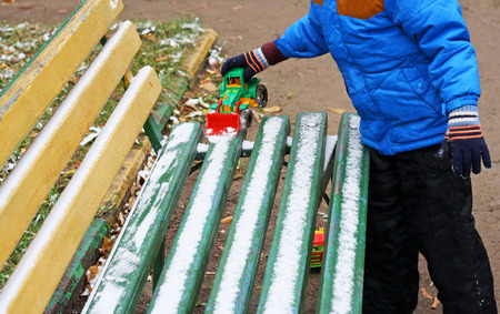 Part of the image of a small child who is standing near a wooden bench, covered with snow. The child clears snow from a bench using a toy excavator.