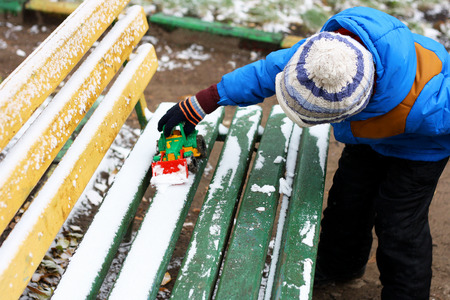 rummage: Image of a small child that stands near the colorful benches, covered with snow, and plays with a red toy construction equipment.