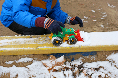 Part of the image of a small child who sits between the first snow and sand and plays with red toy construction equipment. Visible hand, dressed in a blue jacket, black pants and boots. Stock Photo