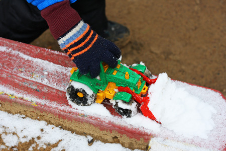 Part of the image of a small child who sits between the first snow and sand and plays with red toy construction equipment. Visible hand, dressed in a blue jacket. Stock Photo