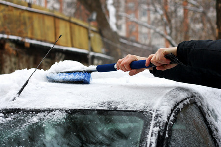 snowcovered: Winter. Snow-covered car. A man cleans the car from snow with the help of special brushes.