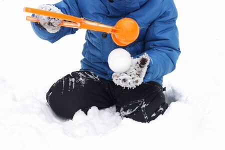 Childrens winter games outdoors. The image of the child who is using a plastic toy makes balls-snowballs from snow. Stock Photo