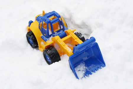 Great childrens bright toy excavator, which stands on the ground in the snow.