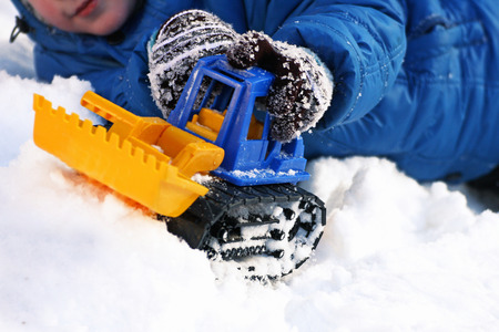 Childrens games in the winter. Part of the image of a small child laying in the snow and plays with toy construction equipment.