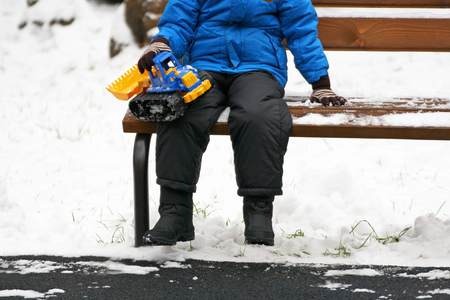 rummage: Part of the image of a small child, who sits on the bench in warm winter clothes among the white snow. Child holding a toy car of construction machinery. Stock Photo