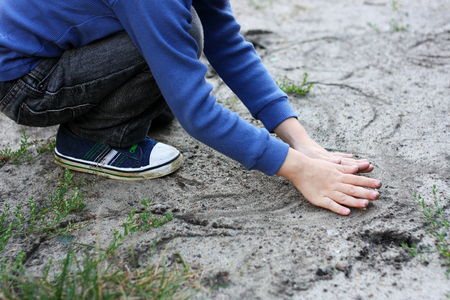 Developmental activities in the fresh air. The child sits down and draws a finger in the sand of different shapes. 版權商用圖片