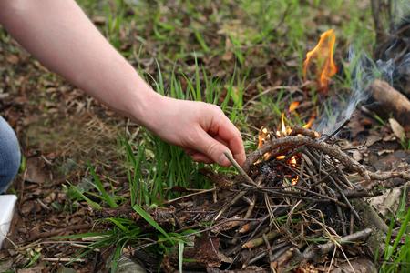 L'homme dans les bois. Les mains d'un homme qui dans la forêt parmi les feuilles sèches et flétries allument le feu. Banque d'images - 74181433