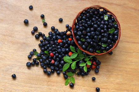 The wooden surface on which the scattered blueberries and strawberries. Next some berries are in a small wicker basket. Stock Photo