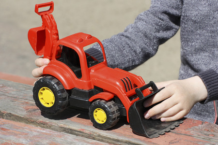 Image of a small child, who sits outdoors at the old table with wooden surface. A child plays with a red toy construction vehicles. Stock Photo