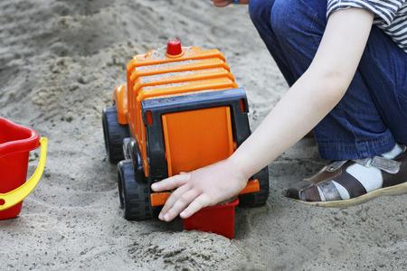carretilla de mano: Camina para los niños al aire libre. Parte de la imagen de un niño pequeño que se sienta y juega con un gran coche de juguete en la arena. Foto de archivo