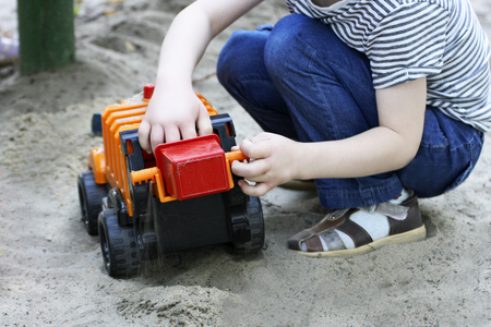Walks for children in the fresh air. Part of the image of a small child who sits and plays with a big toy car in the sand .