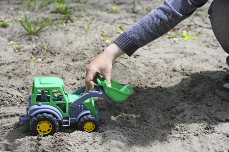 Children playing with toys outdoors. The child sits among the sand. The image of the little child who sits and plays with a green toy shovel on the sand .