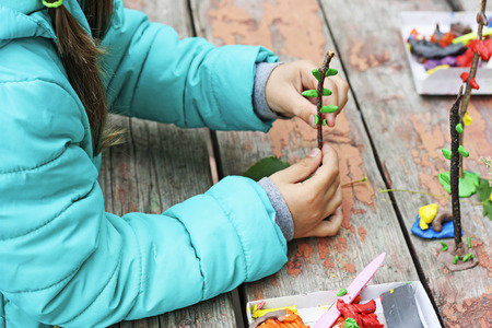 slovenly: Child to play outdoors. The image is part of small child playing with plasticine in the street behind the mahogany Desk. A child plays with clay and various natural materials with different shapes.