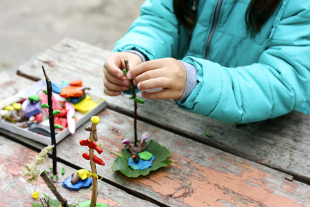 caoba: Child to play outdoors. The image is part of small child playing with plasticine in the street behind the mahogany Desk. A child plays with clay and various natural materials with different shapes.