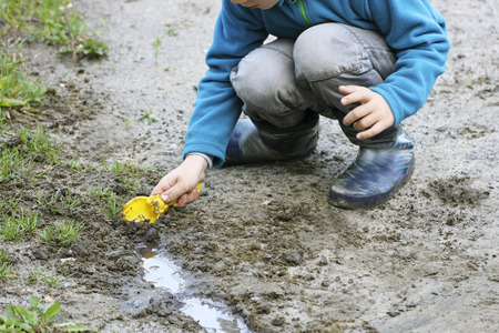 makes: Walk with the children. A small child sitting on his haunches near a small muddy puddles. The kid scoop makes a trickle. Stock Photo