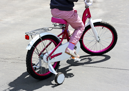 Sports kids outdoors. Girl rides a pink childrens bike on the paved road. Stock Photo