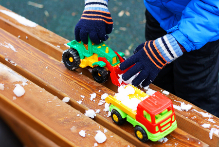 Childrens games in the cold season. Part of the image of a small child standing next to a wooden bench covered with snow. The child clears snow from a bench using a toy excavator. Stock Photo