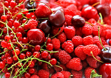 Berry background.Berries of ripe red raspberry, currants and cherries are poured into one big pile.