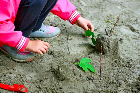 The child plays on the Playground in the warm season. The child plays with sand and plants. 版權商用圖片