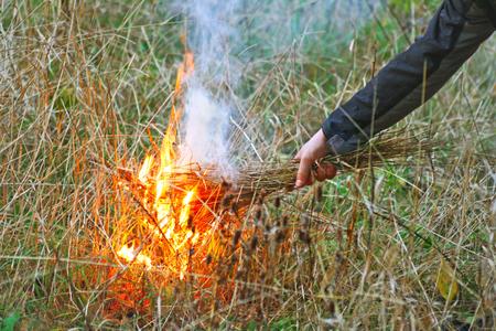 Man sets fire to dry grass.Fire on dry grass. Stock fotó