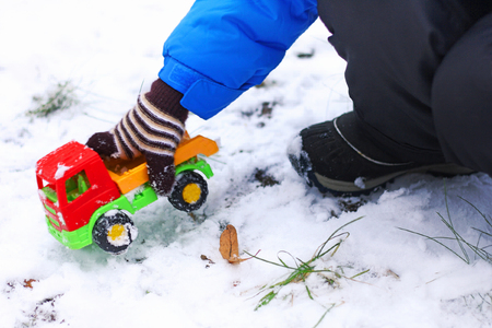 Games in the snow. Part of the image of a child who plays among the first snow with a red machine.
