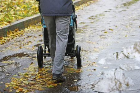Walking father with child in the fresh air. A man carries a baby carriage on an asphalt road, through puddles.