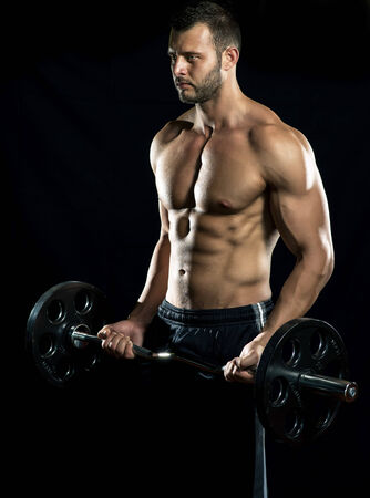 Man doing weight lifting in gym on black background  Imagens