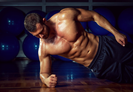 Man doing side plank exercise in gym Stock Photo
