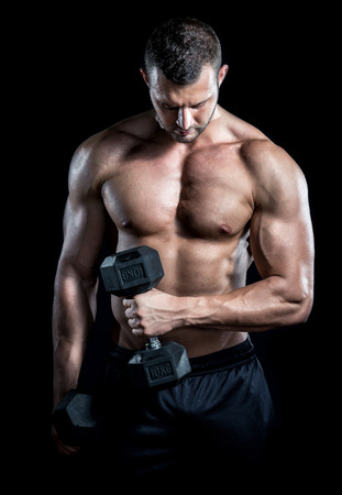 Young adult man doing barbell press in gym. Black background. Gym training workout. Stock Photo