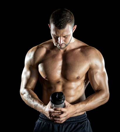 protein: Young adult man drinking protein shake in gym. Black background.