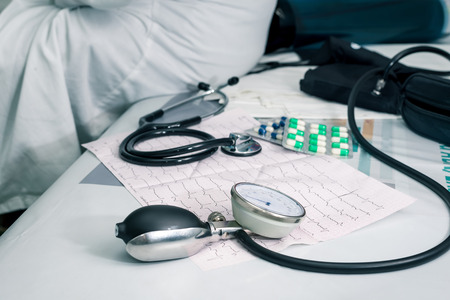 desease: Stethoscope, pills and ECG chart on desk Stock Photo