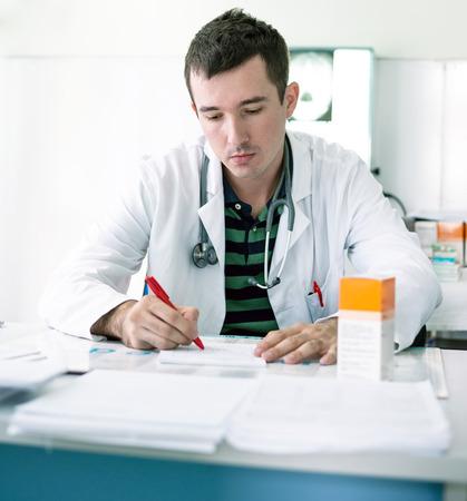 prescribe: Young doctor prescribing recipe in his ordination.